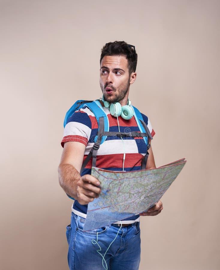 有背包的男性游人读地图的 库存图片
