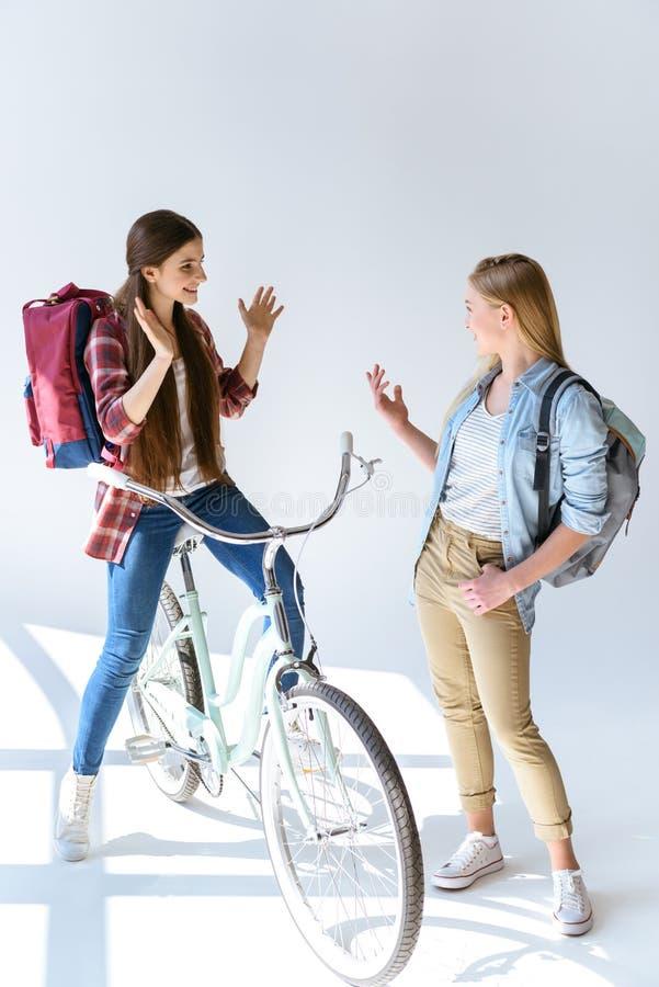 有背包的白种人十几岁的女孩谈和看彼此的 免版税库存照片