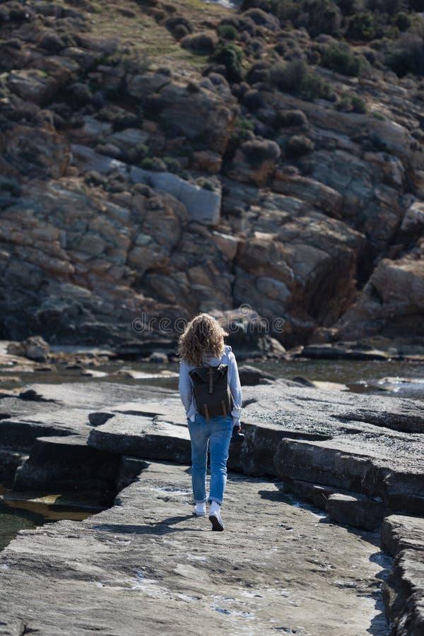 有背包的白肤金发的妇女游人走在岩石成畦状起伏岸的 免版税库存照片