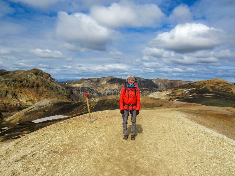 有背包的站立的年轻女人在注视着在美丽的流纹岩彩虹山的山峰夏天 免版税图库摄影