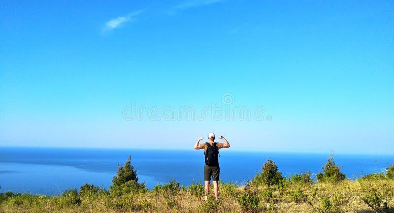 有背包的行家年轻人享受在山峰顶的日出  男性旅游旅客在登山以后显示二头肌 免版税库存照片