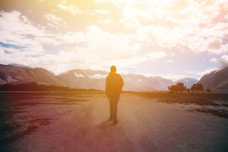 有背包的走反对阳光的男性旅客剪影在山高地区域 免版税图库摄影