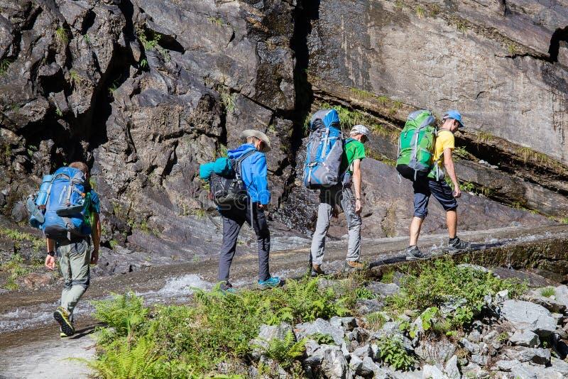 有背包的远足者在喜马拉雅山的迁徙的足迹 尼泊尔 免版税库存图片