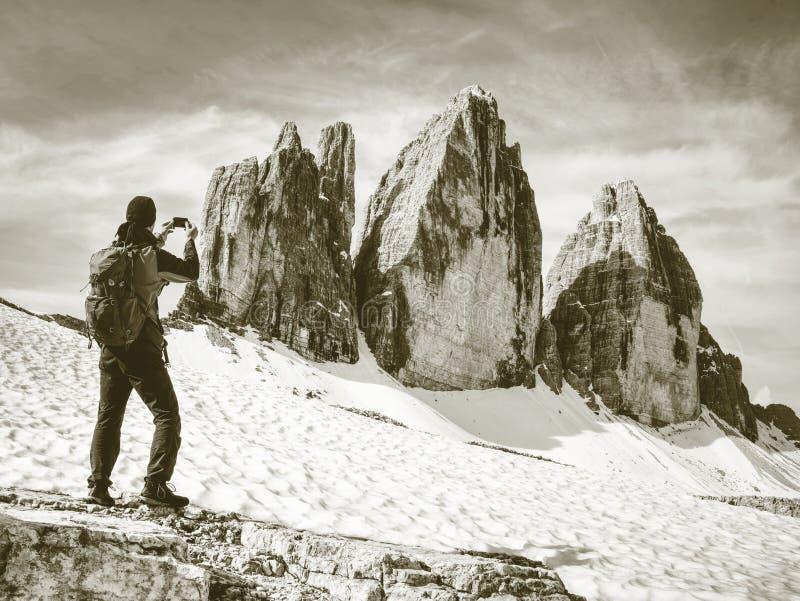 有背包的远足者在山峰附近的足迹 免版税库存图片