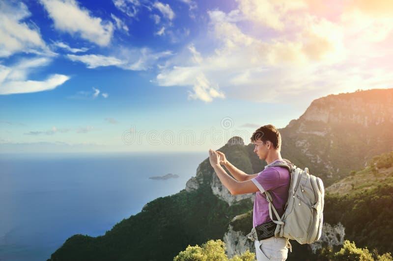 有背包的远足者在山顶部 免版税库存照片