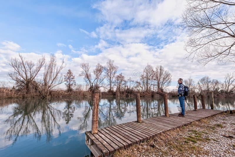有背包的远足者在河岸的木码头  免版税图库摄影