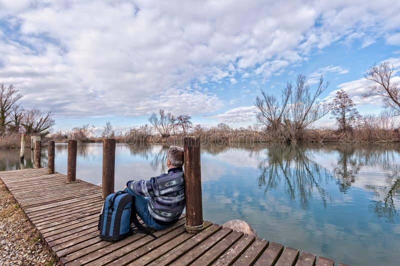 有背包的远足者在河岸的木码头  免版税库存图片