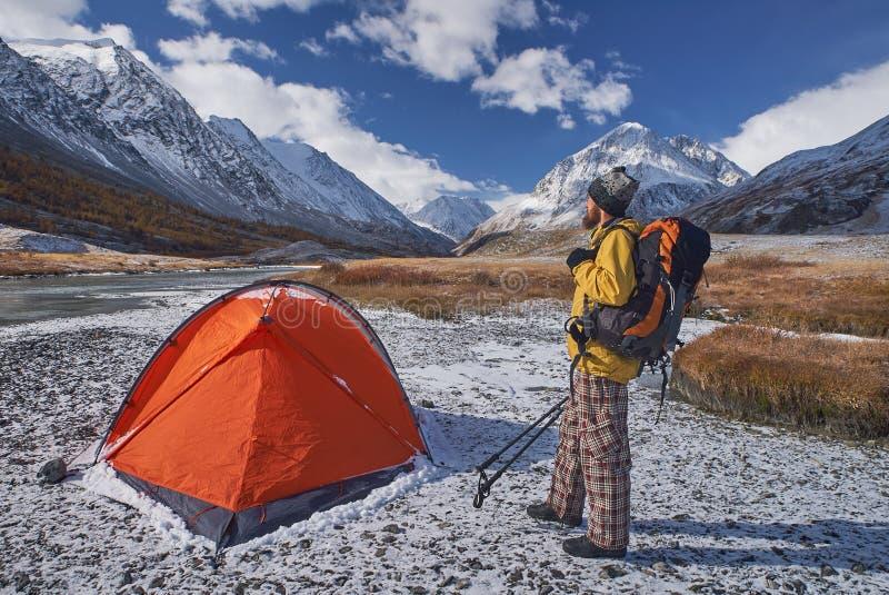 有背包的远足者在野营在春天期间的山 库存照片