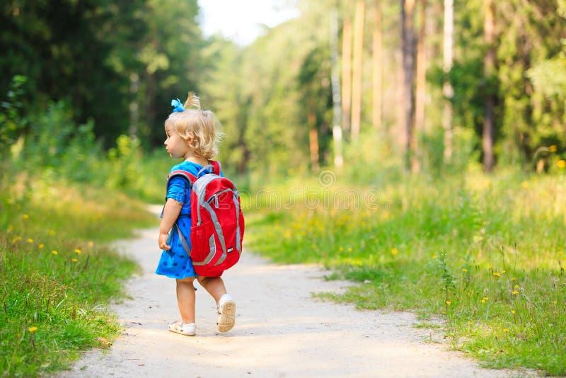 有背包的逗人喜爱的小女孩在夏天森林里 图库摄影