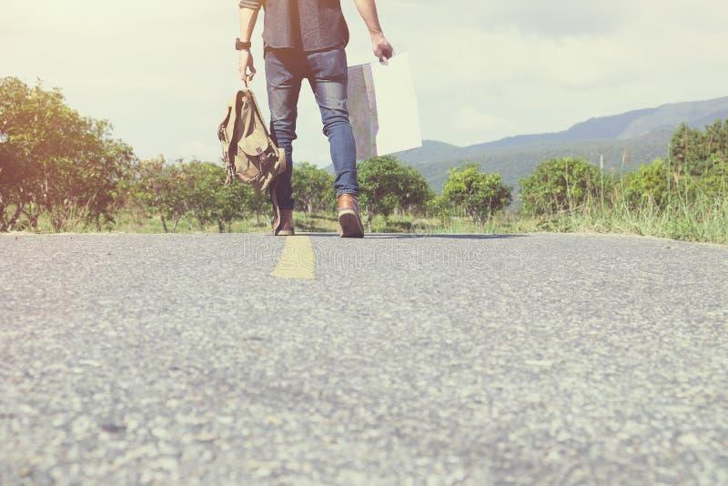 有背包的年轻人旅客走在路的室外 免版税库存照片