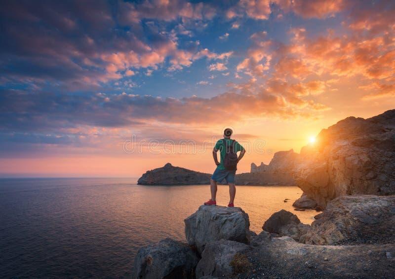 有背包的年轻常设人在日落的石头 免版税库存照片