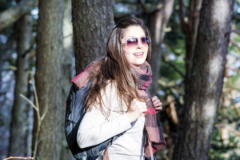 有背包的年轻旅游妇女在森林里 图库摄影