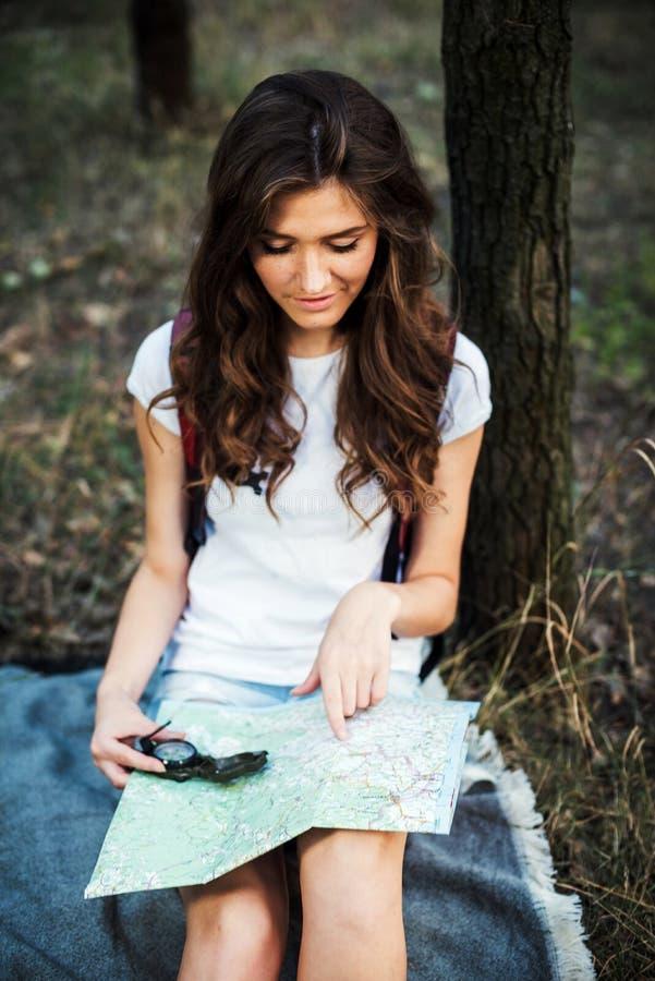 有背包的年轻白种人在木头的女性和地图 图库摄影