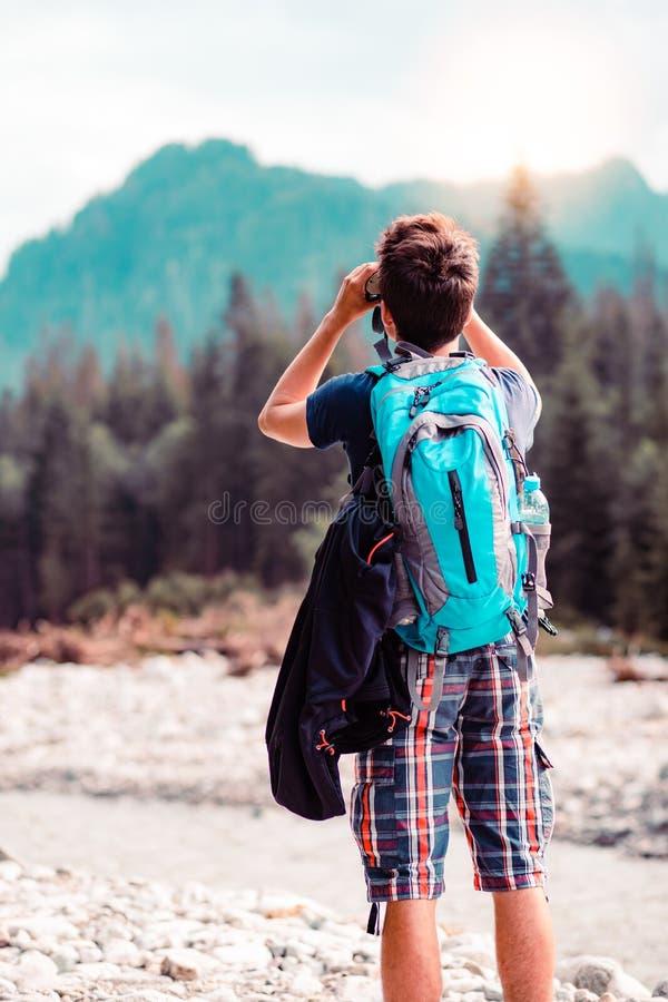 有背包神色的年轻流浪汉通过双筒望远镜 图库摄影