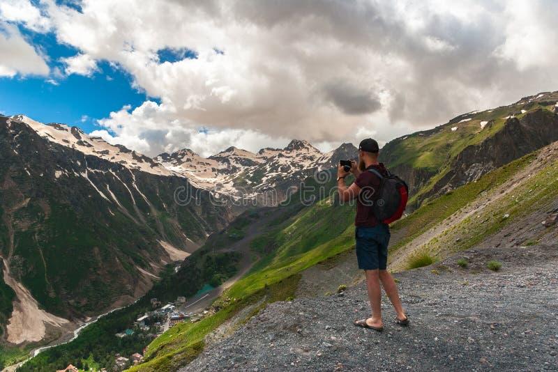 有背包立场的游人在高原和照片山顶部 高加索山脉,峡谷巴克桑河 免版税图库摄影