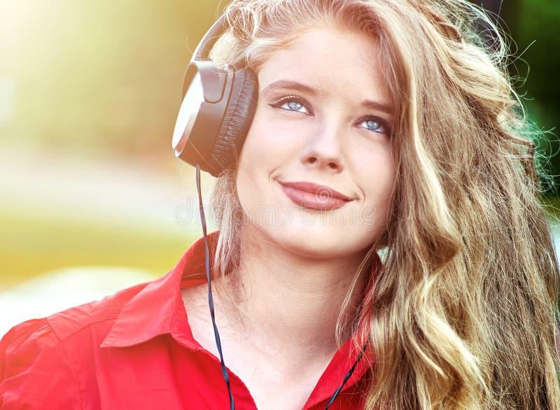 有背包耳机的学生女孩听在绿草的音乐 库存照片