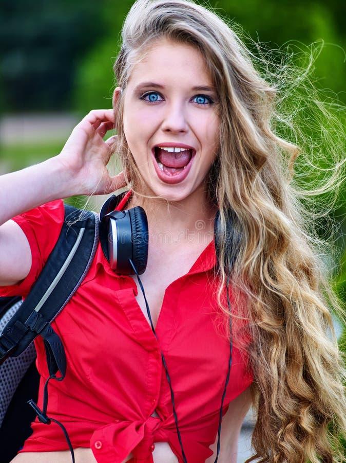 有背包耳机的学生女孩听在绿草的音乐 图库摄影