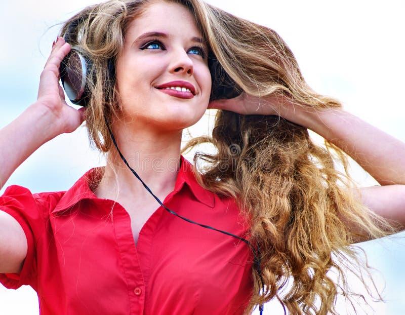 有背包耳机的学生女孩听在绿草的音乐 免版税库存图片
