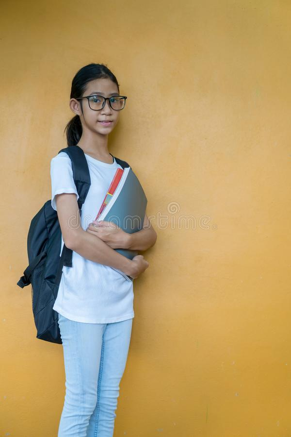 有背包藏品书的亚裔矮小的女小学生 免版税库存照片