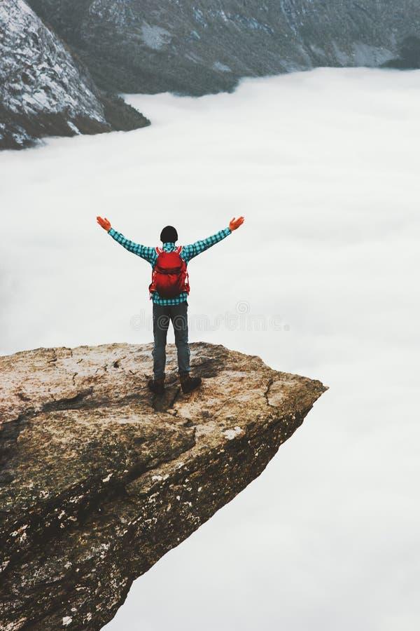 有背包远足者的人Trolltunga岩石峭壁边缘的 图库摄影