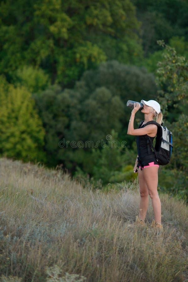 有背包饮用水的妇女游人本质上 图库摄影