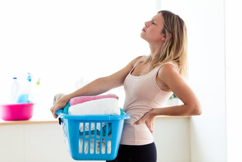 有背部疼痛藏品篮子的美丽的年轻疲乏的妇女与干净的衣裳在家 免版税库存照片
