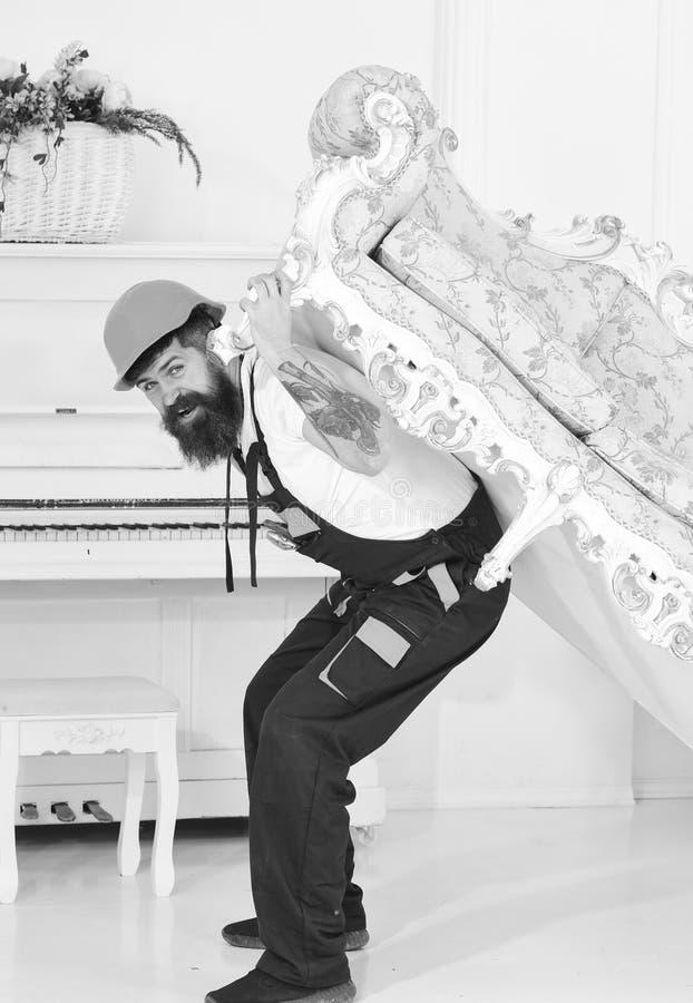 有胡子、工作者总体的和盔甲的人运载沙发支持,白色背景 送货业务概念 装载者 图库摄影