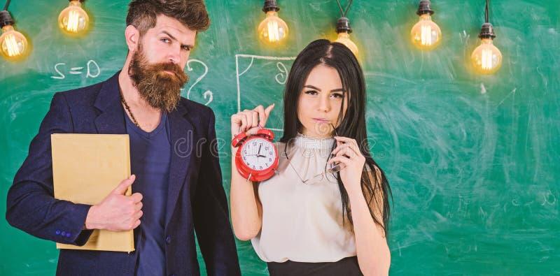 有胡子举行书和女孩老师的人拿着闹钟,在背景的黑板 学校统治概念 夫人 免版税库存照片