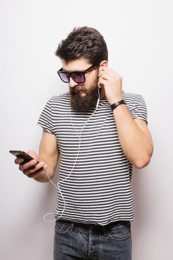 有胡子佩带的衬衣和太阳镜的愉快的行家享受音乐的 免版税库存照片