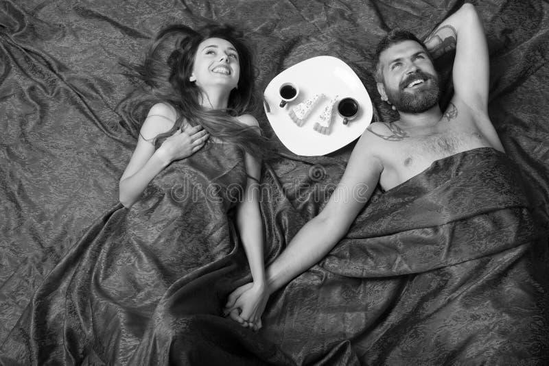 有胡子和愉快的面孔的人食用与微笑的夫人,顶视图的浪漫早餐 男人和妇女有一半的报道了身体 免版税库存照片