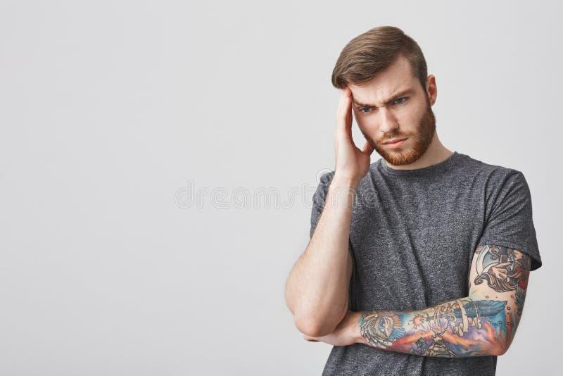 有胡子和时兴的发型的悦目被刺字的成熟哀伤的人按摩前额用手的,看在旁边 库存图片