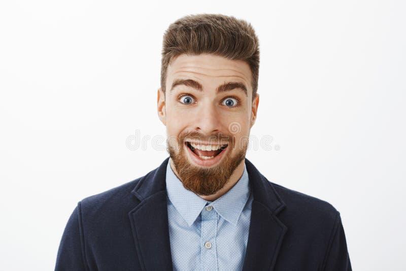 有胡子和深蓝眼睛的热心激动和惊奇的愉快的英俊的人广泛地微笑从触目惊心的 免版税库存照片