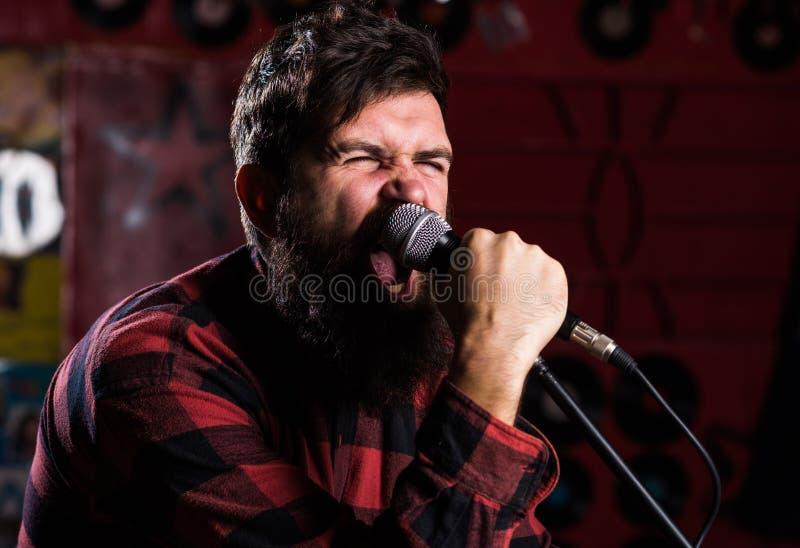 有胡子和髭唱歌歌曲的音乐家在卡拉OK演唱 摇滚明星概念 有紧张的面孔的人拿着话筒 库存图片