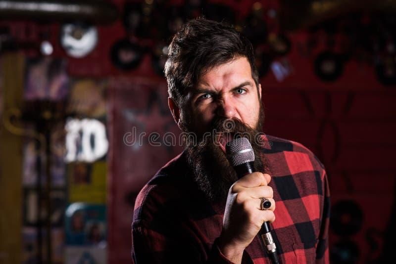 有胡子和髭唱歌歌曲的音乐家在卡拉OK演唱 库存照片