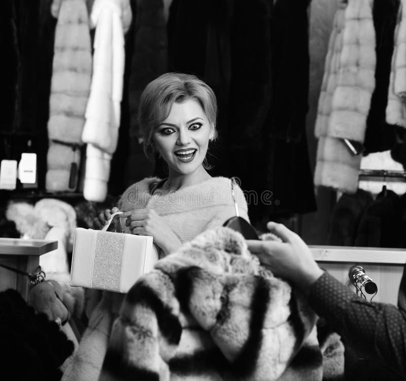 有胡子和髭的售货员显示皮大衣给夫人 桃红色毛皮的女孩在男性手上看外套 免版税库存图片