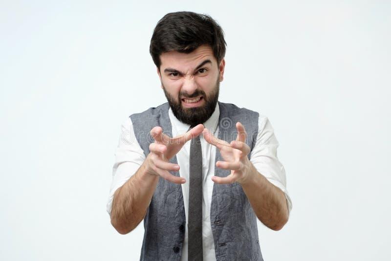 有胡子和黑发的恼怒的人,拉扯往照相机的手堵塞某人 免版税库存照片