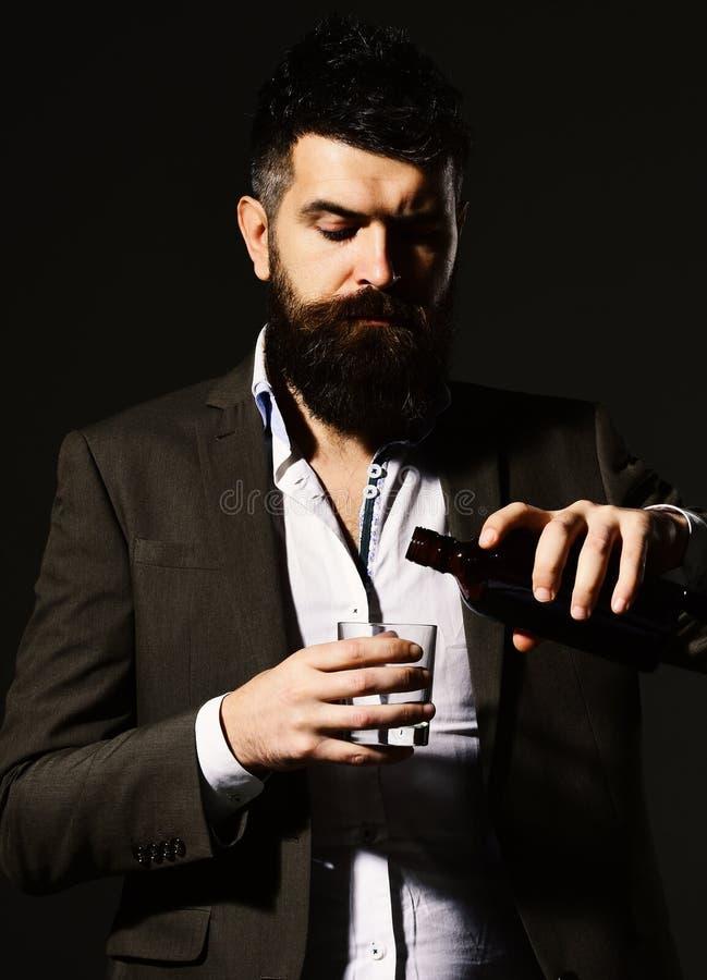 有胡子品尝酒精的斟酒服务员 与严肃的面孔的商人 免版税图库摄影