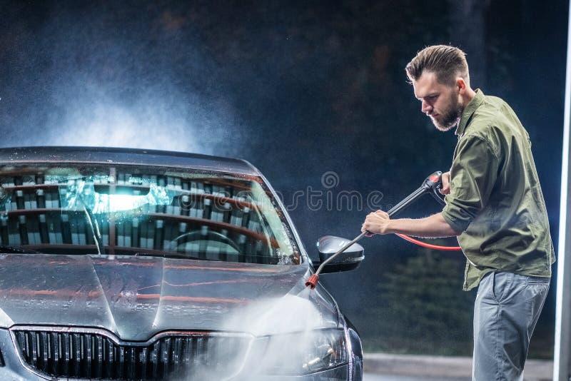 有胡子或汽车洗衣机的一个人在商店洗涤的晚上洗涤有一台高压洗衣机的一辆灰色汽车 免版税库存图片