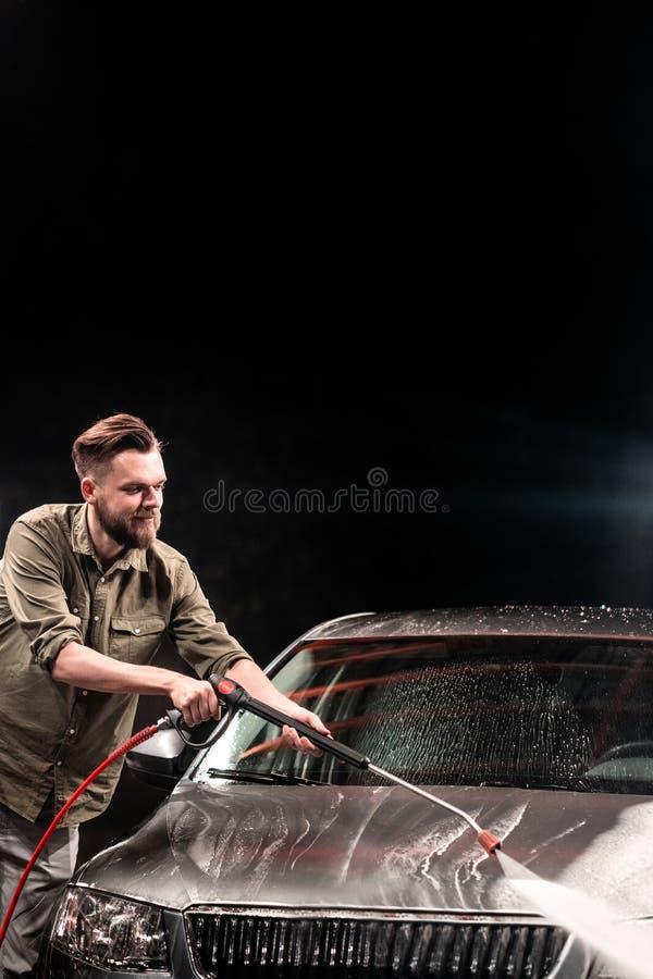 有胡子或汽车洗衣机的一个人在晚上洗涤有一台高压洗衣机的一辆灰色汽车在街道 免版税库存照片
