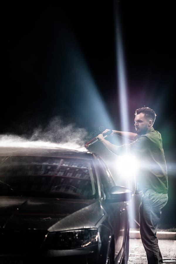 有胡子或汽车洗衣机的一个人在洗车的晚上洗涤有高压用具的一辆灰色汽车 免版税库存图片