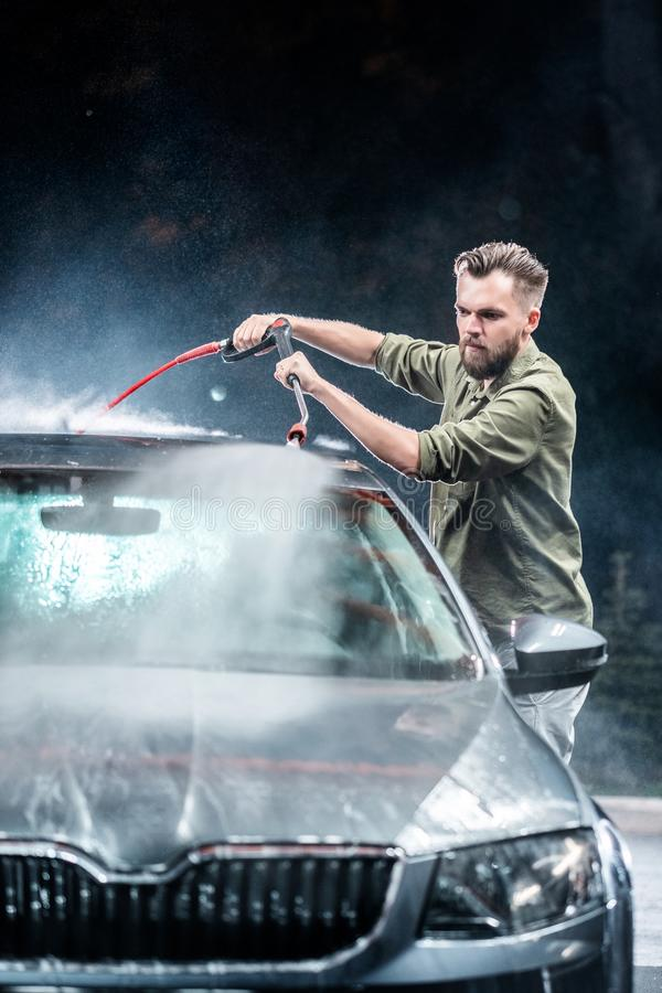 有胡子或汽车洗衣机的一个人在洗车的晚上洗涤有高压用具的一辆灰色汽车 免版税库存照片