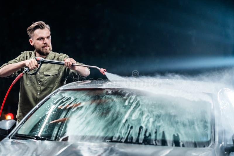 有胡子或汽车洗衣机的一个人在洗车的晚上洗涤有高压用具的一辆灰色汽车 库存照片