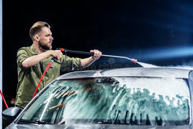 有胡子或汽车洗衣机的一个人在洗车的晚上洗涤有高压用具的一辆灰色汽车 免版税图库摄影