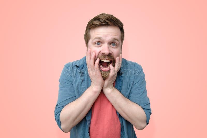 有胡子的一个愉快,吃惊的白种人人,情感地握他的在他的面孔的手并且张了他的从宜人的嘴 图库摄影