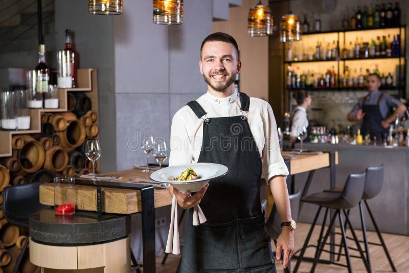 有胡子的一个英俊的年轻人在站立在餐馆和拿着有飞蛾的围裙穿戴了一块白色板材 库存图片