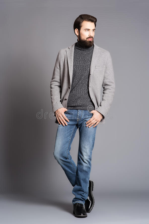 有胡子的一个年轻人,佩带夹克和牛仔裤站立 库存图片