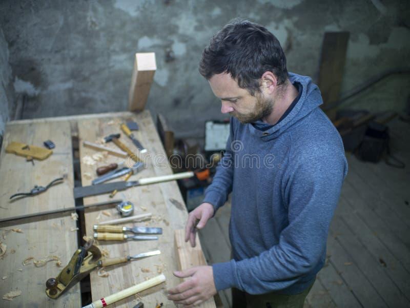 有胡子的一位木匠站立在与工具的木匠业桌上 库存图片