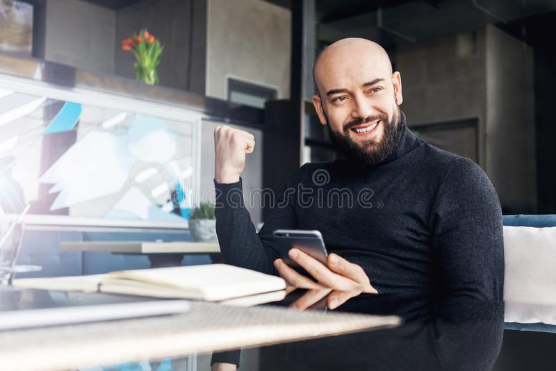 有胡子的中年人拿着智能手机并且是情感地愉快的关于赢得,赢得,当坐在咖啡馆在桌上时 免版税库存图片