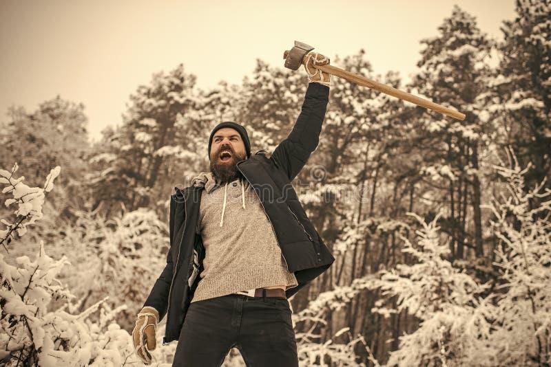 有胡子的人伐木工人举行轴在多雪的冬天森林里,野营 免版税图库摄影