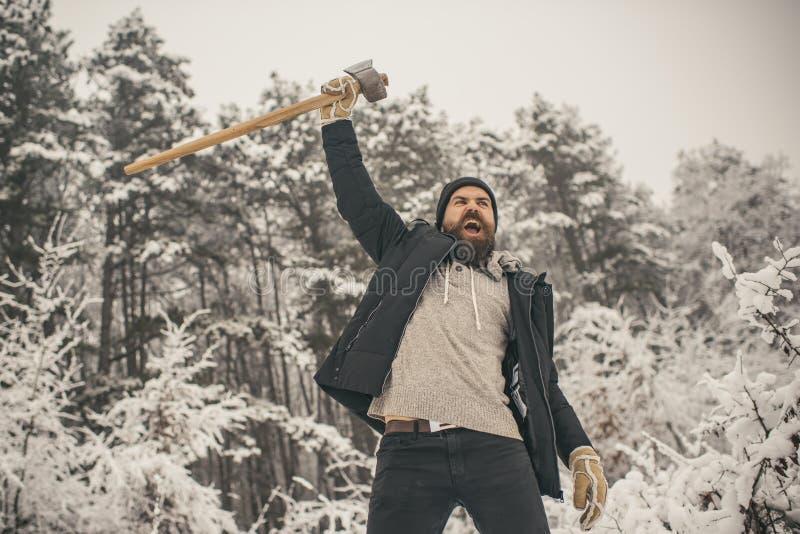 有胡子的人伐木工人举行轴在多雪的冬天森林里,野营 免版税库存照片